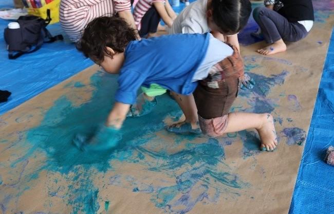 両手に絵の具を付けて描く男の子